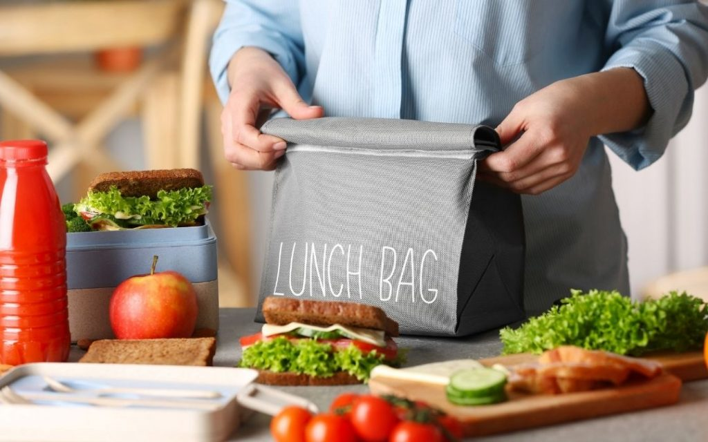 mom packing a black lunch bag with white writing