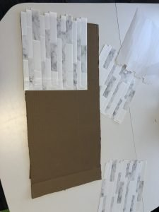Using a peel and stick backsplash to create a 'faux' tile backsplash on a piece of cardboard for the play kitchen.