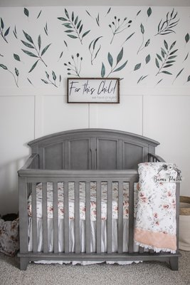 Front view of grey wood baby crib. Decorated with girlie floral sheets and blanket. White board and batten with botanical wall decals on feature wall behind crib.