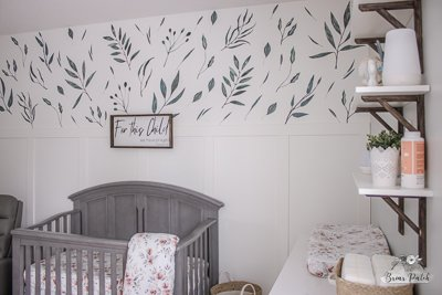 Nursery feature wall with floral accents.